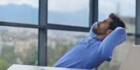 22186092-feliz-empresa-joven-hombre-trabaja-en-la-oficina-moderna-en-el-ordenador-Foto-de-archivo
