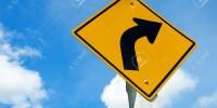 16114087-Carretera-se-al-de-advertencia-de-curva-peligrosa-hacia-la-izquierda-en-el-cielo-azul-Foto-de-archivo