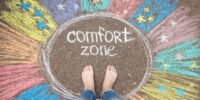 Comfort zone concept. Feet standing inside comfort zone circle surrounded by rainbow stripes painted with chalk on the asphalt.